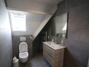 badkamer met radiator, wastafel en wc